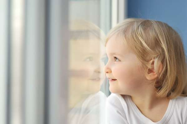Young child looking outside with their nose pressed against the window