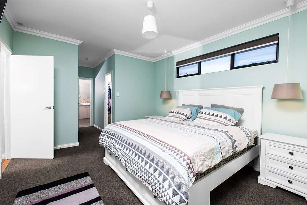Fremantle bedroom with sea blue walls and high windows above the bed.