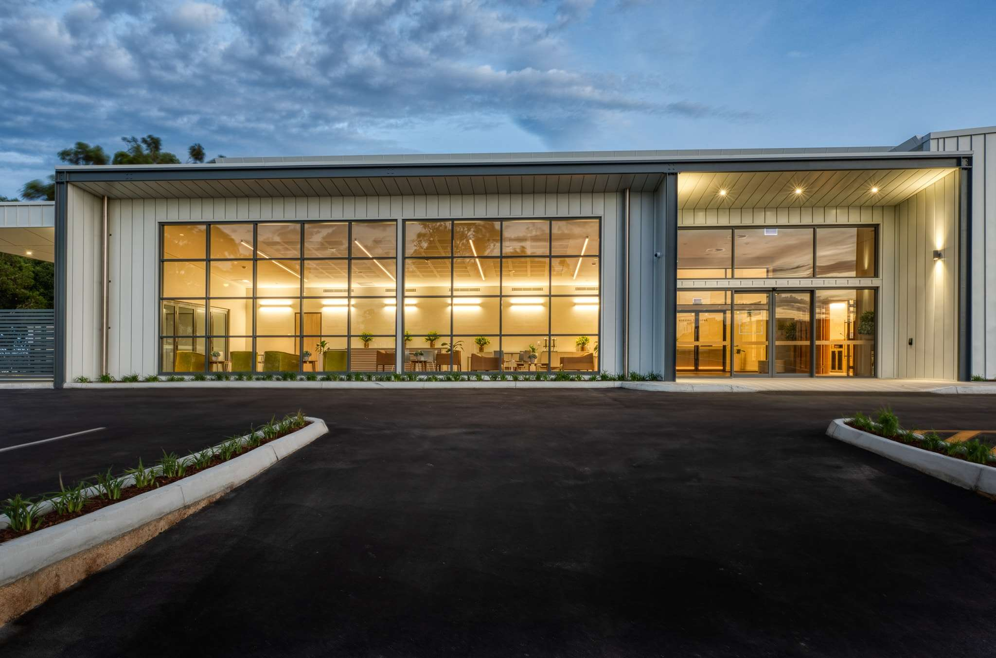 InvoCare Wangara. A twilight photo of the feature wall of windows on this commercial project in Wangara. Products used include Capral AGS 400 series, 225 series doors, Artisan Bi-fold